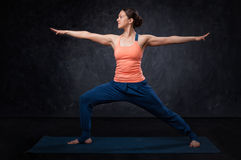 Woman practices yoga asana utthita Virabhadrasana Stock Images