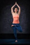 Woman practices yoga asana Vrikshasana tree po Royalty Free Stock Images