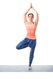 Woman practices yoga asana Vrikshasana tree po Stock Photos