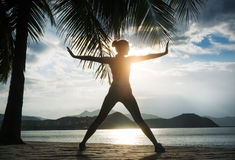 Woman practices yoga on a background sunrise Stock Image