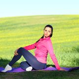 Woman practices yoga. Beautiful woman practices yoga in nature against the yellow field Stock Photo