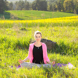 Woman practices yoga. Beautiful woman practices yoga in nature against the yellow field Royalty Free Stock Photos