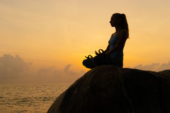 The woman practices yoga at dawn, there is an asana on a stone, dawn and an image of the girl, to enjoy dawn, to be happy with lif Royalty Free Stock Photography