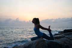 The woman practices yoga at dawn, there is an asana on a stone, dawn and an image of the girl, to enjoy dawn, to be happy with lif Royalty Free Stock Photos