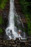 Woman practices yoga at Gitgit waterfall on Bali in indonesia Stock Photo