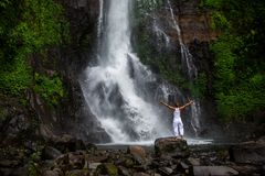 Woman practices yoga at Gitgit waterfall on Bali in indonesia Stock Image