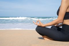 Woman practices yoga and meditates in the lotus position on the beach royalty free stock image