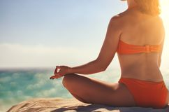 Woman practices yoga and meditates in lotus position on beach royalty free stock images