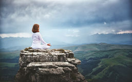 Woman practices yoga and meditates in   lotus position on mounta Stock Photo