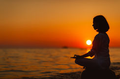 Woman practices yoga and meditates in lotus position on sunset b Stock Photography