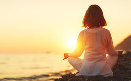 Woman practices yoga and meditates in lotus position on sunset b Stock Photos