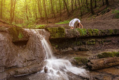Woman practices yoga in nature, the waterfall. forest; Urdhva phanurasana; Dhanurasana pose Royalty Free Stock Image