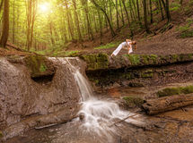 Woman practices yoga in nature, the waterfall. parsvakonasana pose Stock Photo
