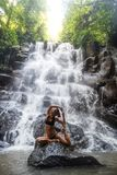 Woman practices yoga near waterfall in Bali, Indonesia royalty free stock photos