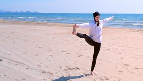 Woman makes yoga on sea beach raises her leg and holds it hand in balance pose. stock video