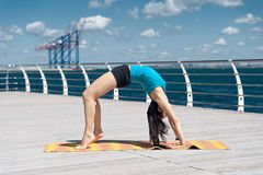 Woman practices yoga on the sea Stock Photo