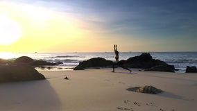 Woman Practices Yoga on Sea Sand Beach at Sunrise. Blond woman practices yoga exercises on wet sand beach among rocks at sunrise against tranquil ocean and vast stock footage
