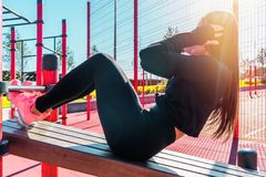 Woman practicing abs workout and exercising outdoors in urban environment. stock images