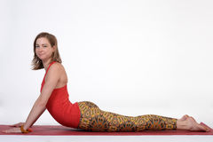 Woman practicing advanced yoga against isolated white studio paper background. Royalty Free Stock Images