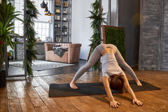 Woman practicing advanced yoga in the living room at home. A series of yoga poses Royalty Free Stock Photography