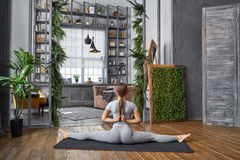 Woman practicing advanced yoga in the living room at home. A series of yoga poses.  stock photography