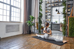 Woman practicing advanced yoga in the living room at home. A series of yoga poses.  stock photo