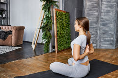 Woman practicing advanced yoga in the living room at home. A series of yoga poses Royalty Free Stock Image