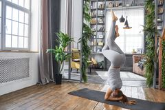 Woman practicing advanced yoga in the living room at home. A series of yoga poses.  royalty free stock image