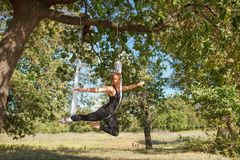 Woman practicing antigravity yoga at the tree near the river. Beautiful blonde girl practicing antigravity yoga at the tree near the river. Advanced Yoga Royalty Free Stock Image