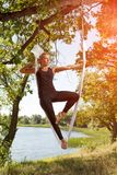 Woman practicing antigravity yoga at the tree near the river. Beautiful blonde girl practicing antigravity yoga at the tree near the river. Advanced Yoga Royalty Free Stock Images