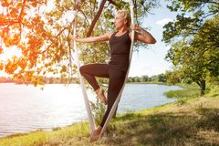 Woman practicing antigravity yoga at the tree near the river royalty free stock images