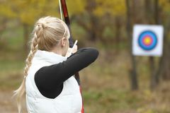 Woman practicing archery outdoors. Woman practicing archery out doors Royalty Free Stock Images