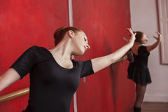 Woman Practicing Ballet Dance In Studio. Young woman practicing ballet dance against red wall in studio Stock Photography