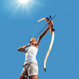 Woman practicing with bow and arrow royalty free stock image