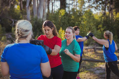 Woman practicing boxing in the boot camp Royalty Free Stock Images
