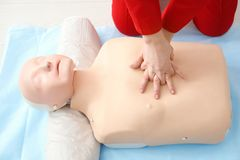 Woman practicing CPR on mannequin stock photography