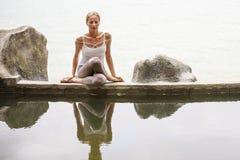 Woman practicing morning meditation Yoga at the beach. Woman practicing or doing morning meditation Yoga in nature at the beach Stock Photo