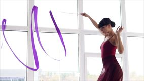 Woman is practicing her rhythmic gymnastic moves. Attractive woman in a red leotard is enjoying her time training. She is waving her ribbon into spirals and stock video