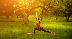 Woman practicing high lunge yoga pose. Young female exercising outdoors. Utthita Ashwa Sanchalanasana. Toned image stock images