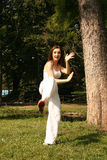 Woman Practicing Kung-Fu. A woman practicing kung-fu or self-defense moves in an outdoor park setting Stock Photos