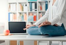 Woman practicing meditation on a desk. Relaxed woman practicing meditation at home, she is sitting in the lotus position on the office desk, mindfulness concept stock photography
