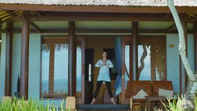 Woman is practicing meditation in yoga position, stretches, on the porch of bungalow on the beach in Bali, nature sounds. Woman is practicing meditation in yoga stock video footage