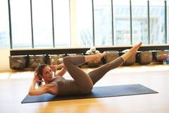 Woman Practicing Pilates on Floor Mat in Studio Stock Photo