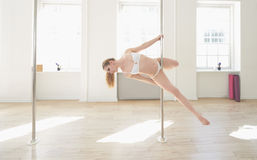 Woman practicing pole dance in a pole fitness cl Royalty Free Stock Photo