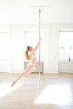 Woman practicing pole dance in a pole fitness cl Stock Photos