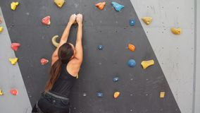 Woman practicing rock climbing on artificial wall indoors. Active lifestyle and bouldering concept. Woman practicing rock climbing on artificial wall indoors stock video