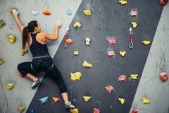 Woman practicing rock climbing on artificial wall indoors. Active lifestyle and bouldering concept. royalty free stock photography