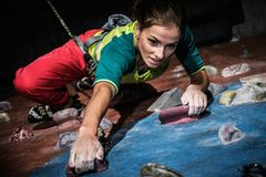Woman practicing rock-climbing on a rock wall royalty free stock image