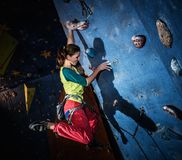 Woman practicing rock-climbing on a rock wall Stock Image