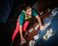 Woman practicing rock-climbing on a rock wall Royalty Free Stock Images